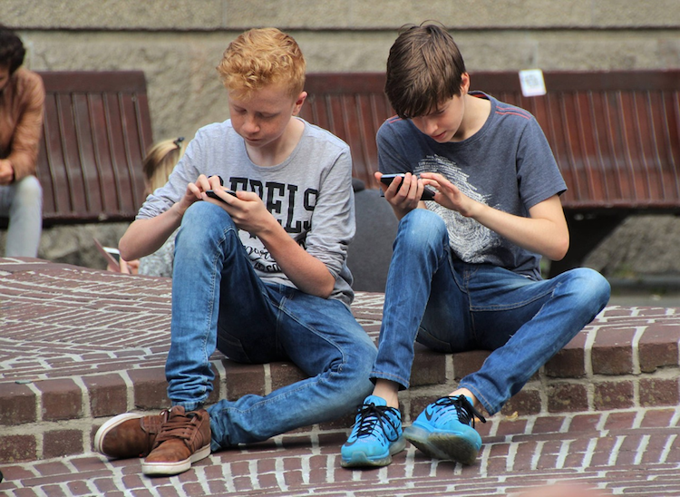 2 young boys sitting on curb using smartphones