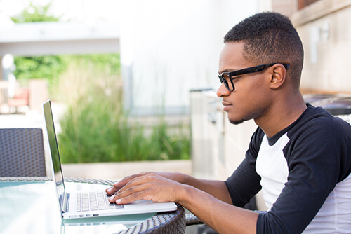 Young college student works on laptop outdoors.