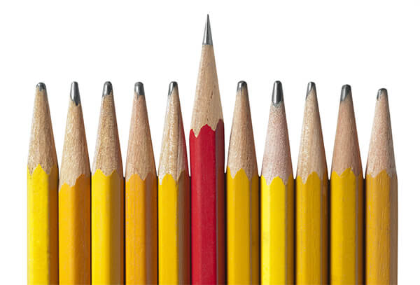 Line-up of 11 sharpened pencils, the middle one being longer and taller than the rest.