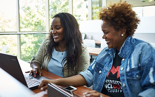 Two female students looking at a laptop together